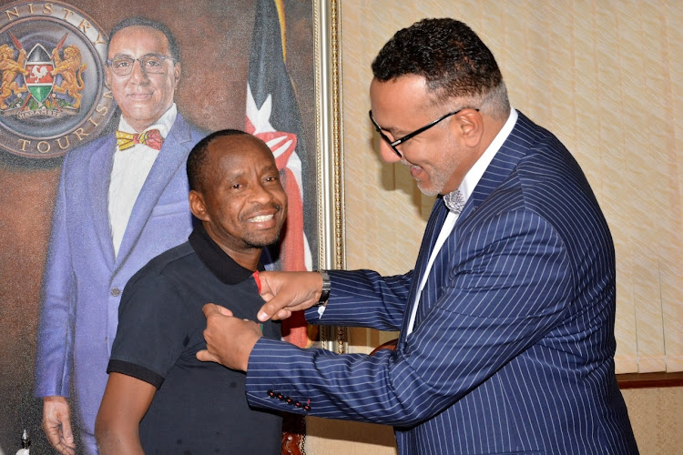 Tourism CS Najib Balala awards Patrick Kilonzo with a presidential award.