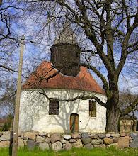 Photo: Die Grünberger Kirche wurde im Jahr 1792 errichtet. Vier Holzsäulen mit schlichten Kapitellen tragen die Decke, den Glockenstuhl sowie die achtseitige Laterne, die sich inmitten des Gebäudes aus dem Ziegeldach erhebt. Gegen 1900 wurde die Kirche wieder hergestellt, die jetzige einfache Innenausstattung stammt aus dieser Zeit. Im Turm befindet sich eine alte Bronzeglocke, in der keine Jahreszahl zu finden ist. Das Gussjahr der Glocke wird dem Mittelalter zugeordnet (wahrscheinlich 14. Jh.) Sie wiegt etwa eine Tonne.  Es findet sich auf der Glocke folgende Inschrift: Defunctos ploro, vivos coop, mugio, probo.  Die Übersetzung lautet: Die Abgeschiedenen beweine ich. Die Lebenden wünsche ich mir herbei. Ich klinge. Ich prüfe.