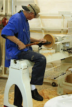 Photo: In order to keep a better arm position, Ron got his right leg over the lathe bed. (I've got to try that too!) The theory here, espoused by David Ellsworth, is that this gives better tool control than leaning way over the lathe with your arm held out far from your body.