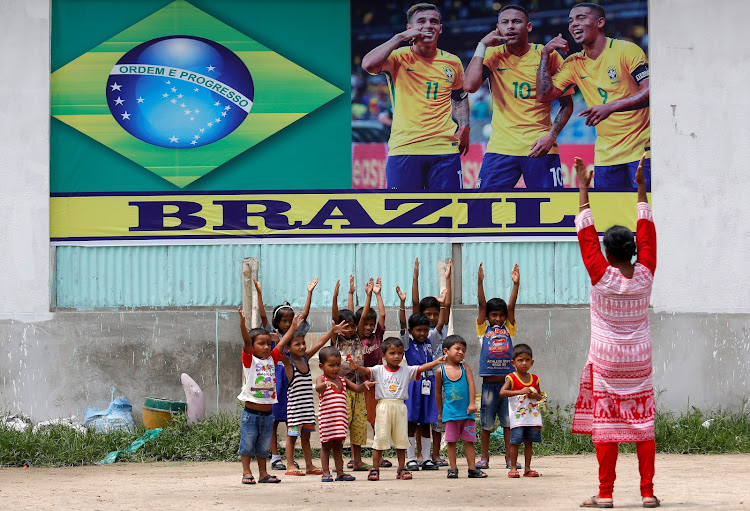 Kolkata schoolchildren exercise in front of a banner of Brazil's soccer players ahead of the Fifa World Cup on Tuesday.
