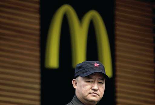 National jobs: A man stands outside a McDonald's restaurant on Wangfujing, a famous shopping street in Beijing, China. A state-backed conglomerate and a US private equity firm have agreed to buy a majority stake of the Golden Arches' assets in the country. Picture: REUTERS
