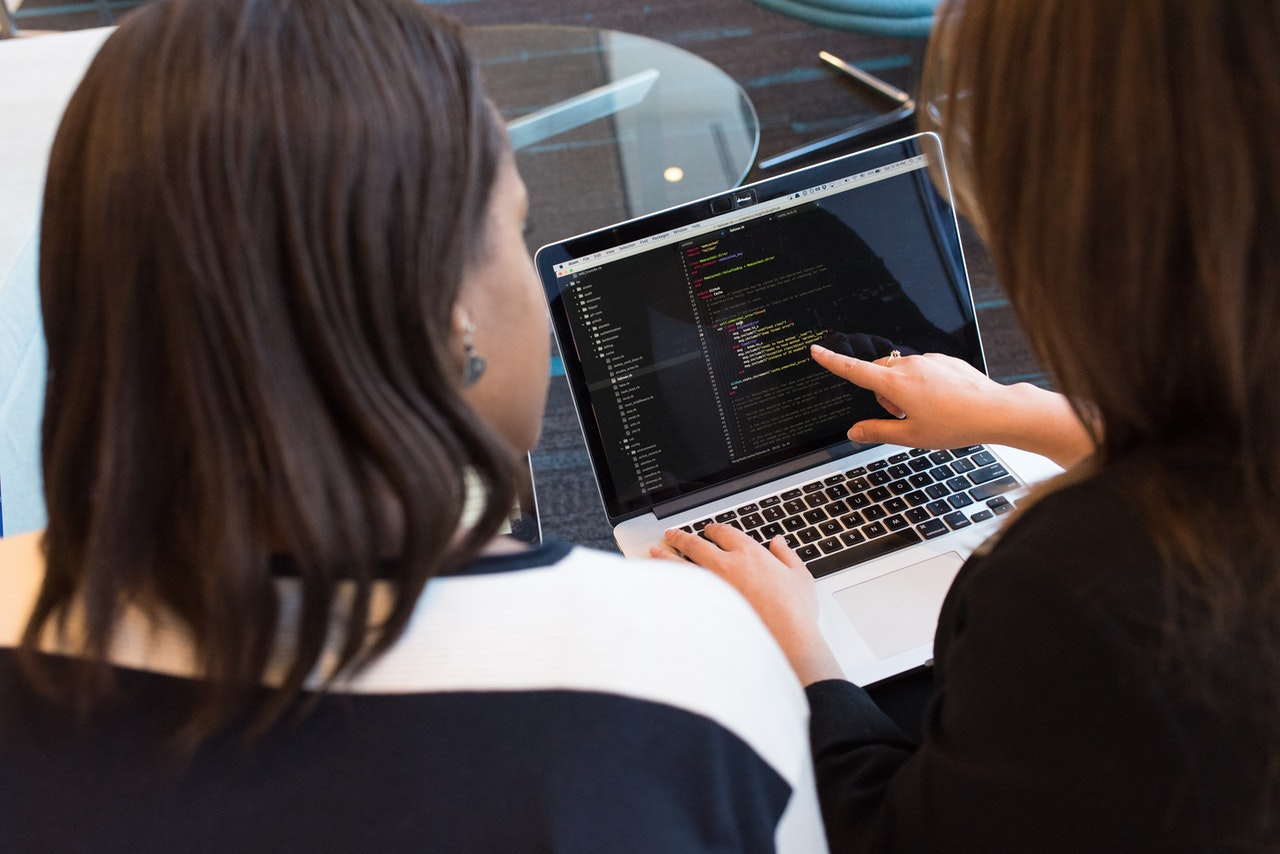 two women looking at code on a laptop
