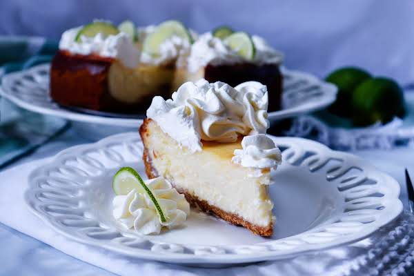 A Slice Of Key Lime Cheesecake On A Plate With Whipped Cream.