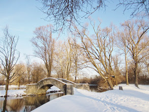 Photo: Snow and stone bridge by a lake in sunlight at Eastwood Park in Dayton, Ohio.