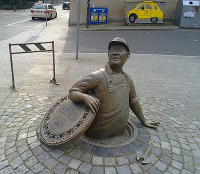 Skulptur eines Arbeiters, der aus einem Gullideckel steigt mit Absperrung und Schraubenschlüssel