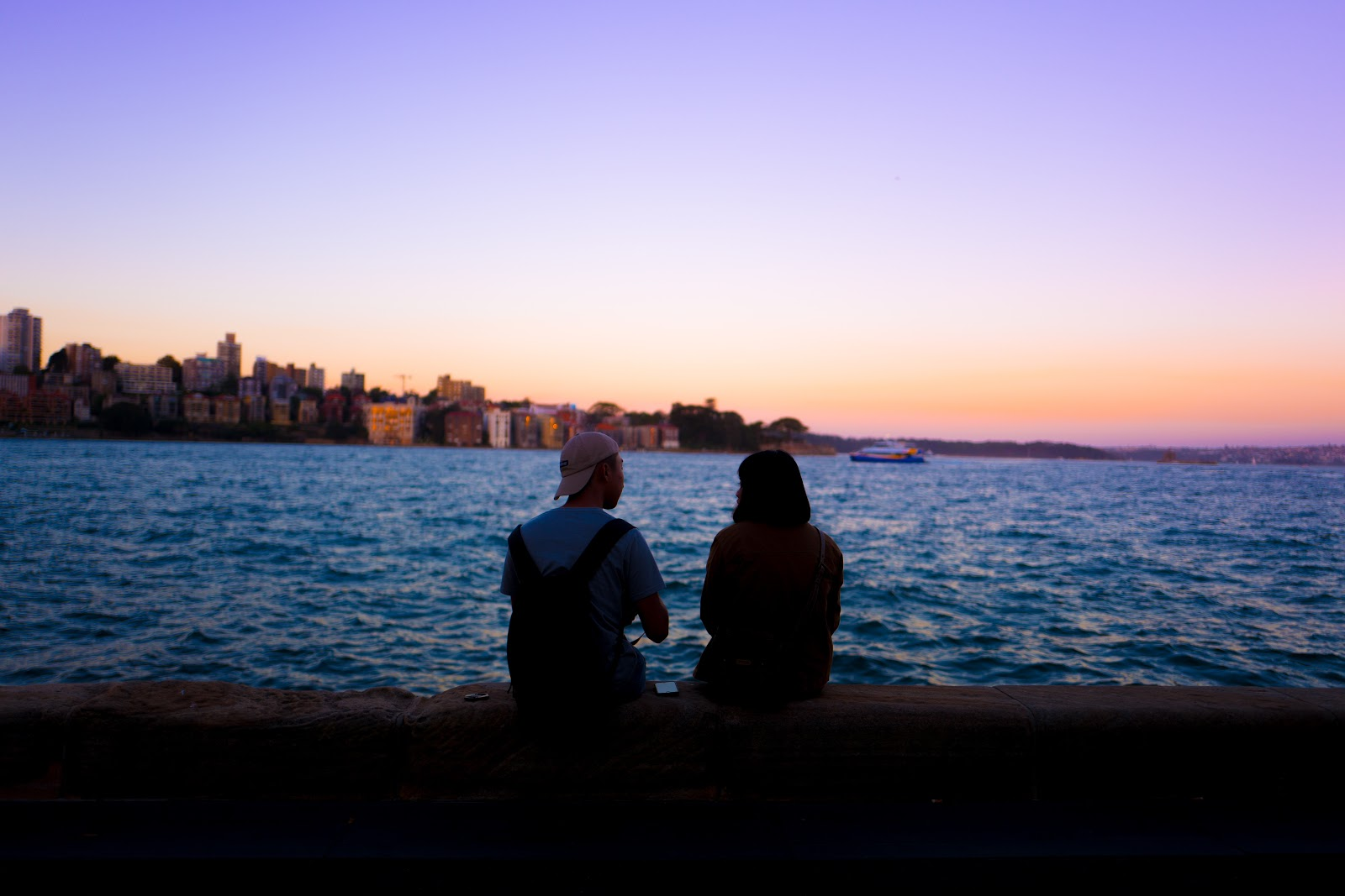 Couple sitting on a harbour wall in Sydney