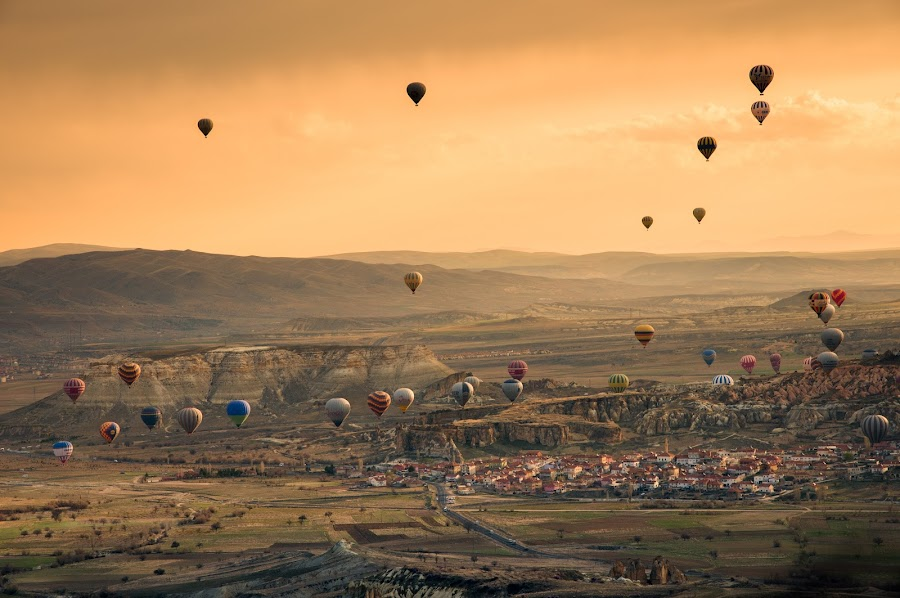 Hot air balloons flying over Cappadocia city by Natapong Paopijit - Landscapes Travel ( nevshehir, mountain, travel, cityscape, landscape, sun, city, aviation, flying, adventure, geography, kapadokya, sky, sunny, dramatic, above, light, geological, activity, hot-air, airship, twilight, journey, scenic, balloon, up, great, fly, sunset, aircraft, summer, hot, air, town, high, view, sunrise, turkey, cappadocia )