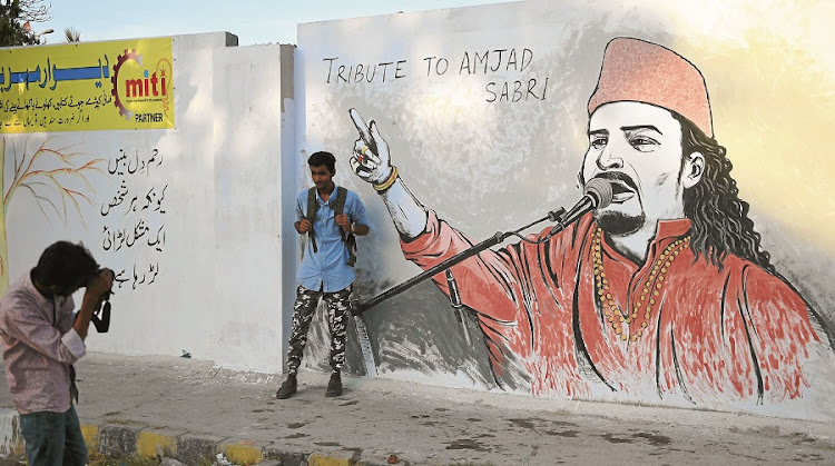 A student takes a photograph of his friend next to a wall image and tribute to  Sufi musician Amjad Sabri  in Karachi. Sabri, one of Pakistan's best-known Qawwali singers, was shot dead close to his home last week. Picture: GALLO IMAGES/AFP/ASIF HASSAN