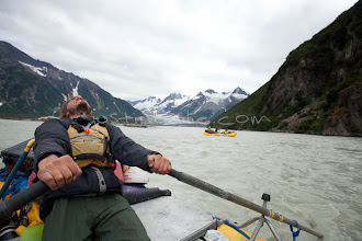 """Photo: River guide pulls on oars after a long day on raft trip down the Tashenshini River. The """"Tat"""" flows out of Yukon, CA, through British Columbia and empties into Glacier Bay National Park in Alaska, US."""