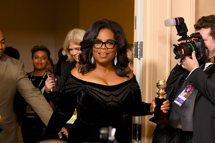 Oprah Winfrey arrives with the Cecil B. DeMille Award in the press room during The 75th Annual Golden Globe Awards