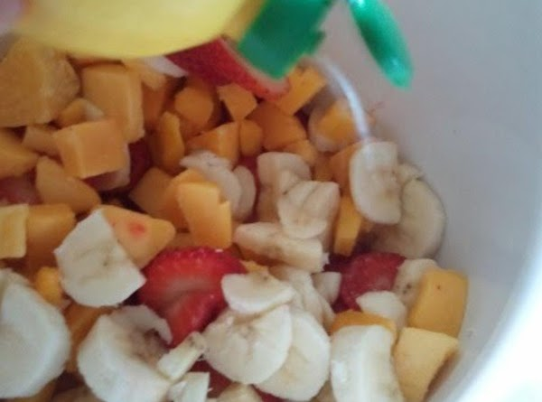 Into bowl, mix the strawberries, mangos and bananas.  Give them a few squirts...
