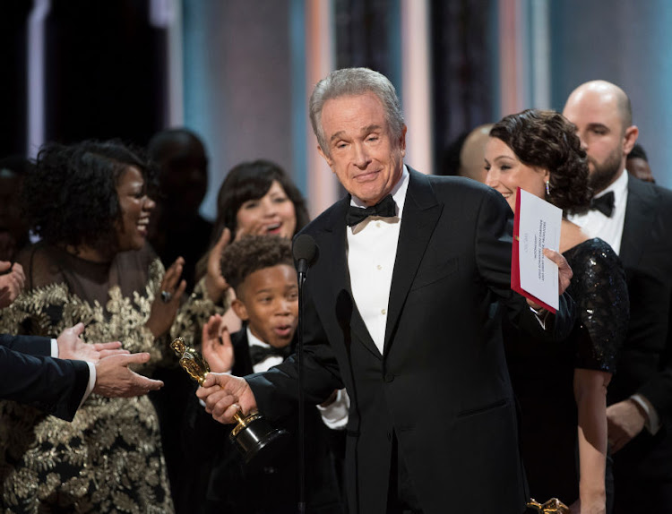 FAKE NEWS: Warren Beatty with the cast and crew of Moonlight, the 'real' winners of the Oscar for Best Picture, after he was given the wrong envelop