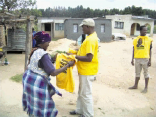 CAMPAIGNING: David Mabuza hands out an ANC T-shirt to Linah Mabasa of Tafelberg. Pic. Unknown. © Unknown.\n\nFM 17/4/2009 PG 17 Millions spentT-shirt supplies run dry.