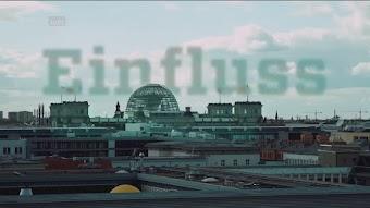 Bild aus Video: Reichstagskuppel hinter Hausdächern. Am Himmel darüber groß das Wort: «Einfluss».