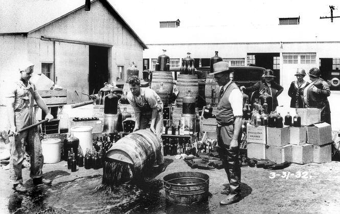 Закон есть закон: Сотрудники Бюро запрета, одного из подразделений ФБР, уничтожают спиртное на складе бутлегеров (фото 1932 года)