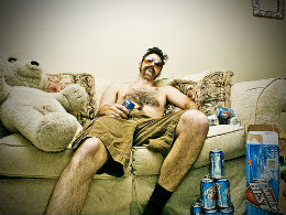 Man drinks beer on couch