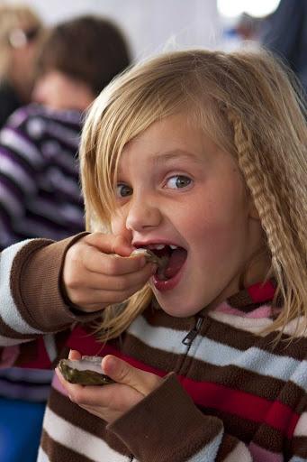 A young girl enjoys shellfish at the annual Shellfish Festival in Charlottetown, Prince Edward Island, Canada.