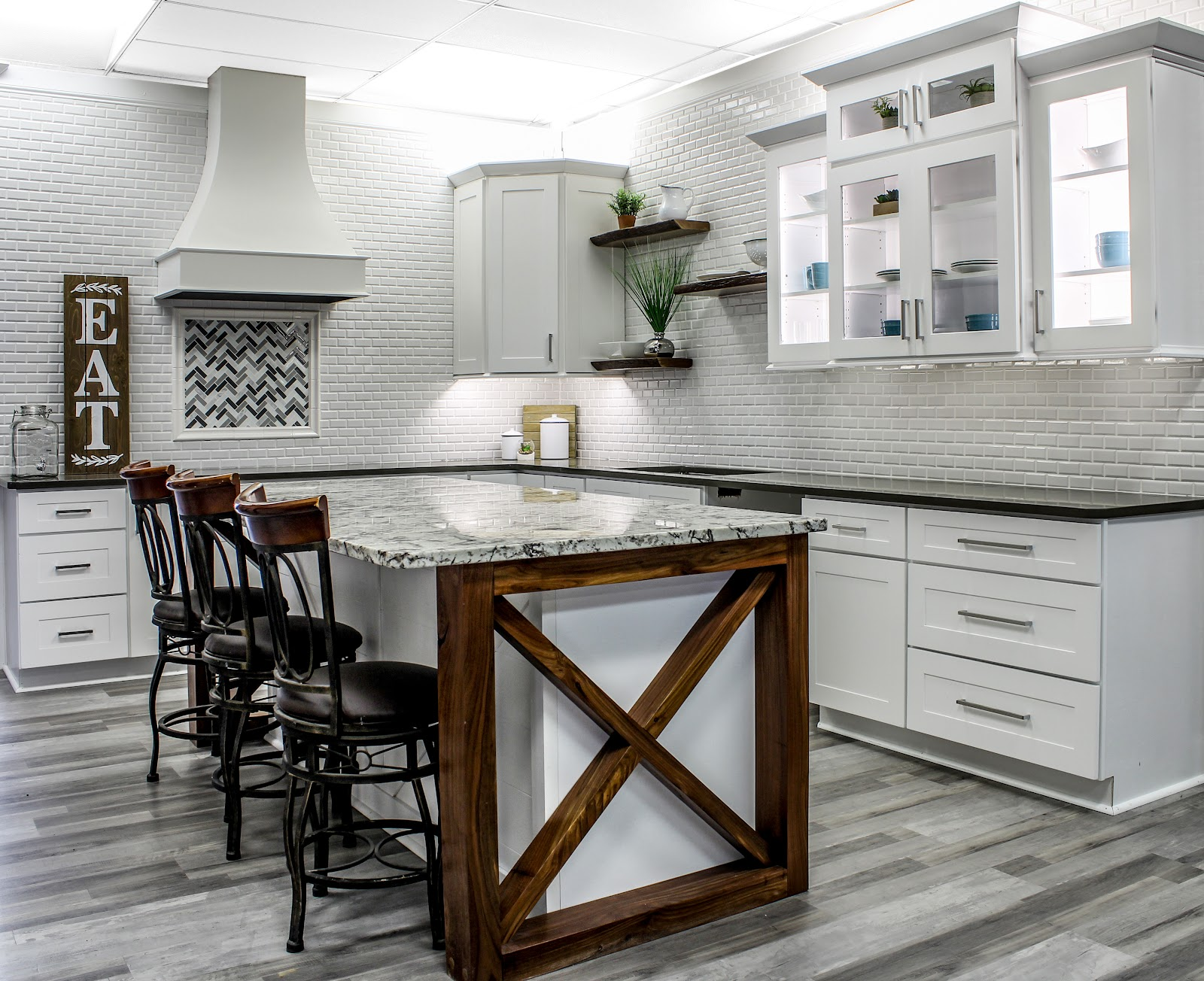 showroom featuring grey flooring, white shaker cabinets and granite countertops with black and white coloring