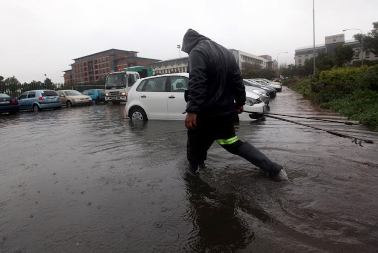 A municipal worker walks through a waterlogged parking area after heavy rains. File photo: THE TIMES