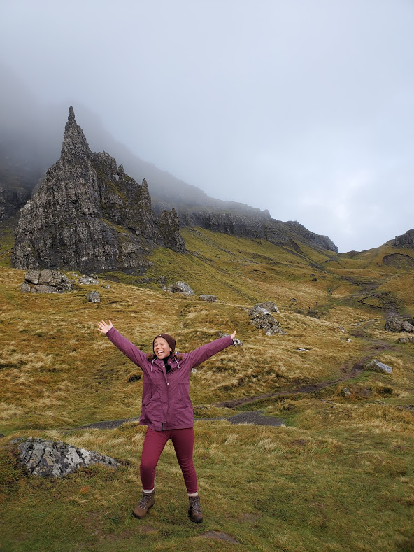 Girl in a purple jacket standing in front of the Old Man of Storr in the Scottish Highlands.