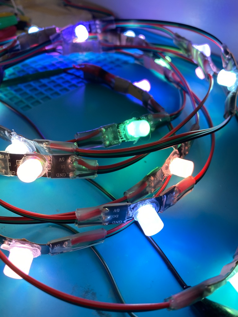 Close up of the coil of illuminated LEDs with diffusers against a blue background