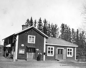 Photo: Affären i Vasselhytte byn 1920. Vasselhyttans första affär låg vid fastigheten Storån 1-4 se bild 540.Affären från 1896 låg på ungefär samma plats som den nuvarnade affärsbyggnaden( Kooperativa o ICA). Affärsdelen på bilden fanns i tillbyggnaden till höger med posten till vänster i den gamla delen. Postemblemet sitter ovanför anslagstavlan.  Poststationen fanns ursprungligen i järnvägsstationen sedan här i gamla affären för att omkring 1934 flytta in i den nya affärsbyggnaden. 1951 flyttade posten åter till järnvägsstation