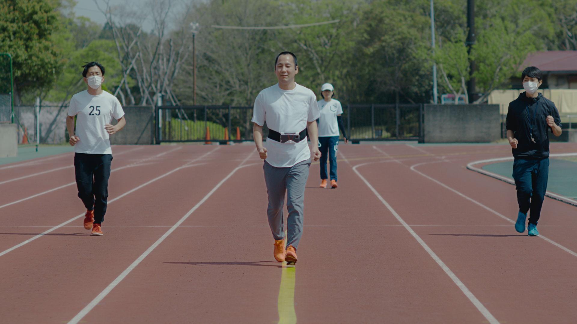 写真:コース上に貼られた黄色いガイドラインのテープに沿って歩く御園さんと、その周りを見守る御園朋子さんとスタッフ。
