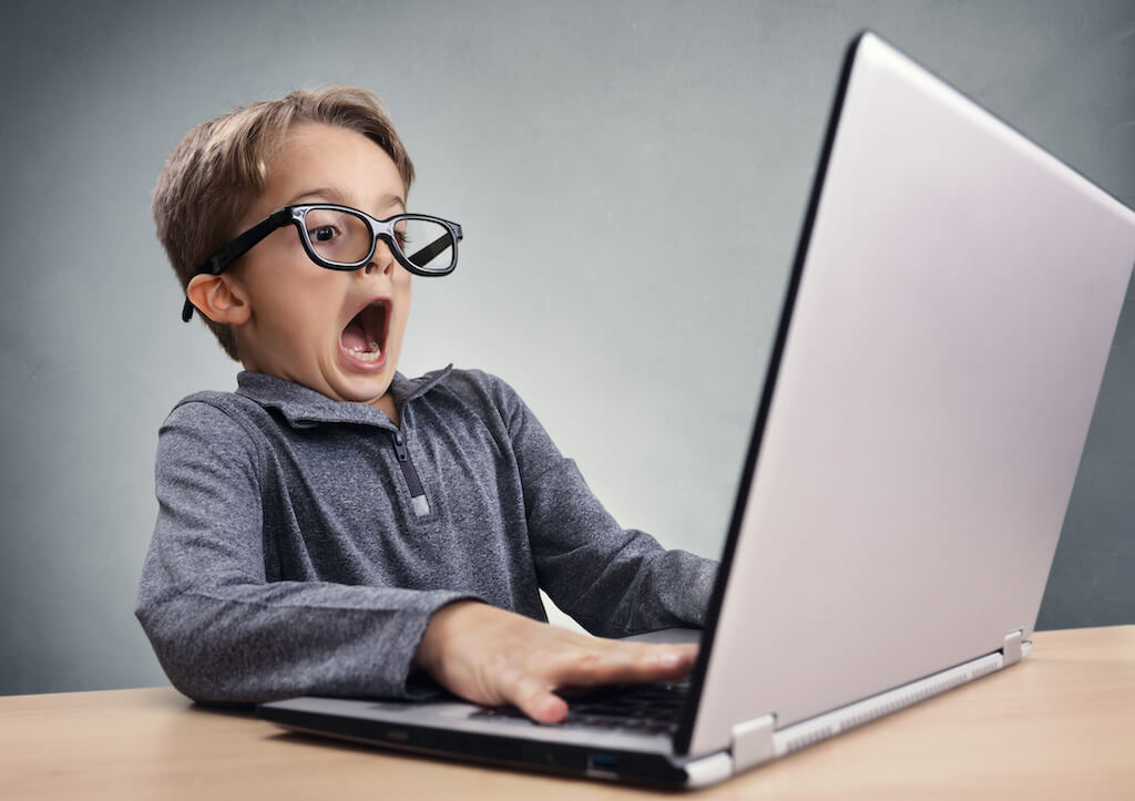 A child looks shocked while problem-solving code on his computer screen