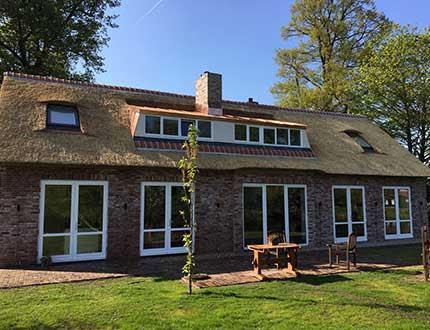 Dom z dachem trzcinowym i ogrodem