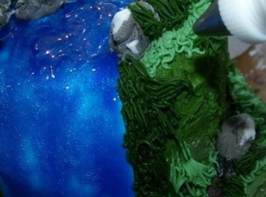 Take the piping bag with darker green icing and pipe grasses along the entire...