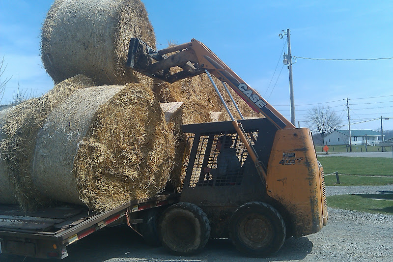 Unloading round bales of straw at a menonite farm in Holmes County