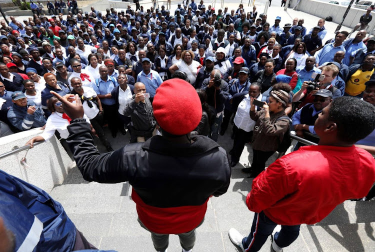 Police keep an eye on bus drivers and other MyCiti staff who are protesting outside the City of Cape Town's civic centre on Tuesday, October 16.