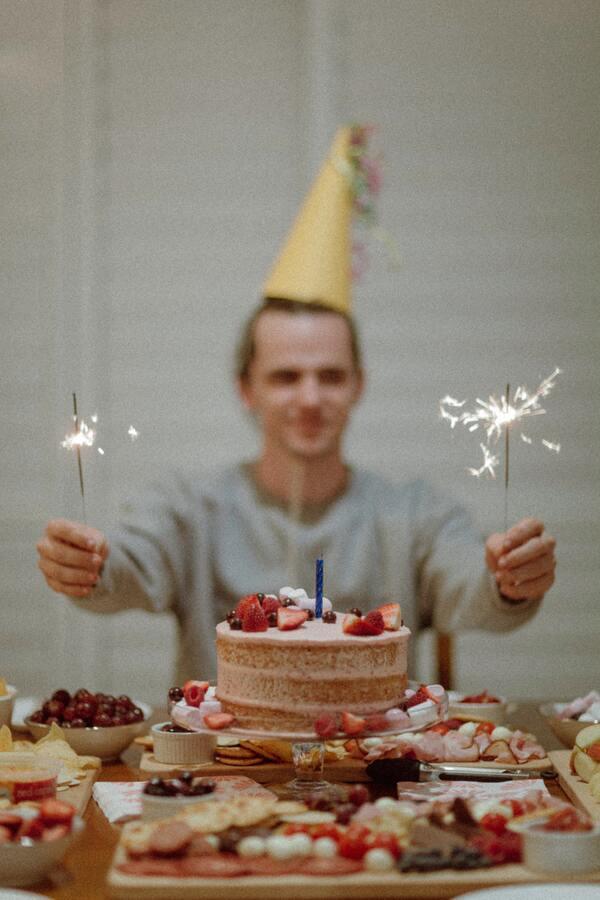 foto de um homem desfocado segurando duas velas de aniversário com uma mesa com um bolo e comidas