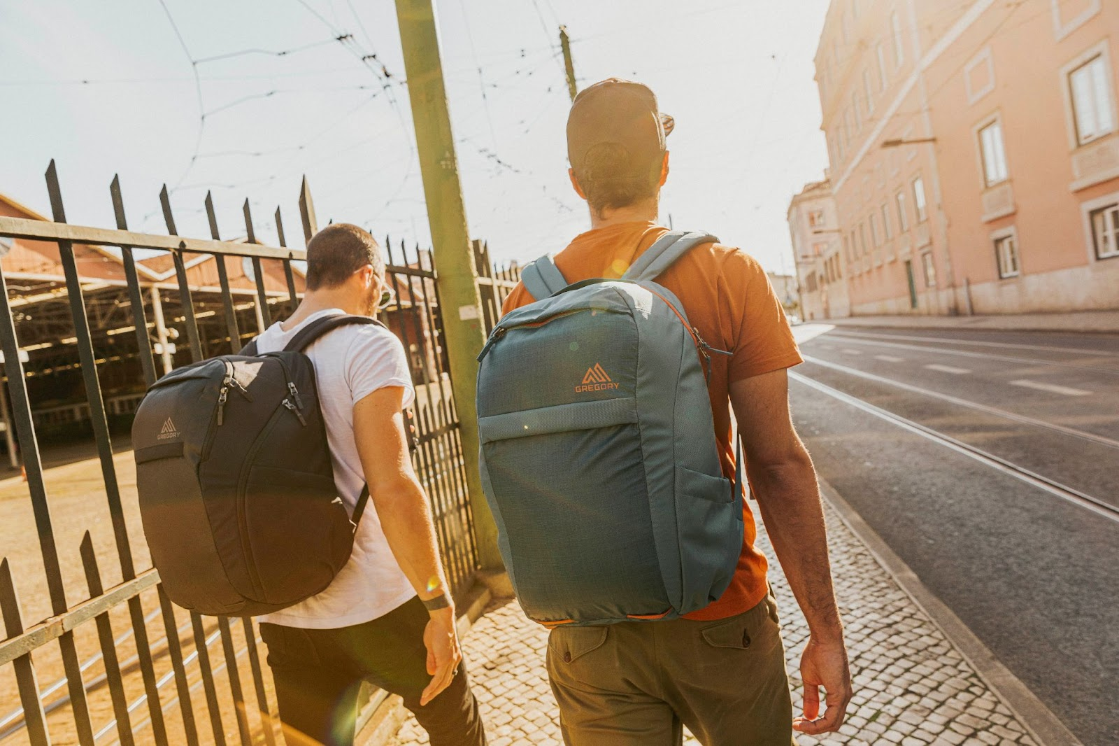 Two men with backpacks walk down a street.