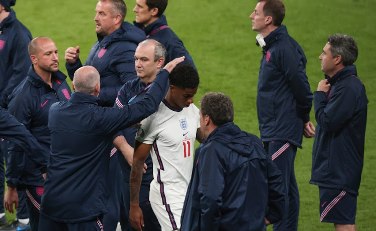Marcus Rashford of England surrounded by the England coaching staff after the penalty shootout during the UEFA Euro 2020 Championship Final between Italy and England at Wembley Stadium on July 11, 2021 in London, United Kingdom.