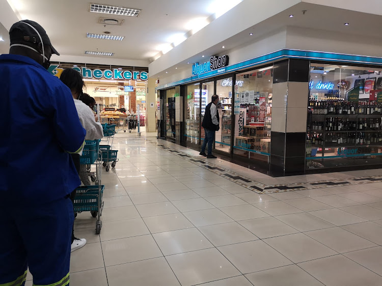 A queue forms outside Checkers Liquor in Northcliff corner, where a customer is seen leaning towards the glass doors to read the alcohol restriction instructions per customer.