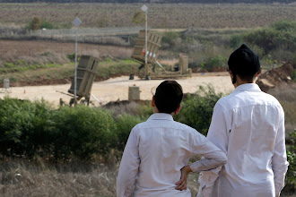 Photo: Ultra-Orthodox Jewish youths look at an Iron Dome anti-missile battery near Tel Aviv.