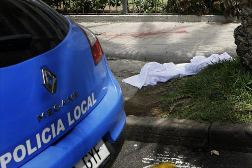 A white sheet covers the place where a man deposit the head of a British woman after decapitated her in a supermarket in Los Cristianos, on the Spanish resort island of Tenerife.