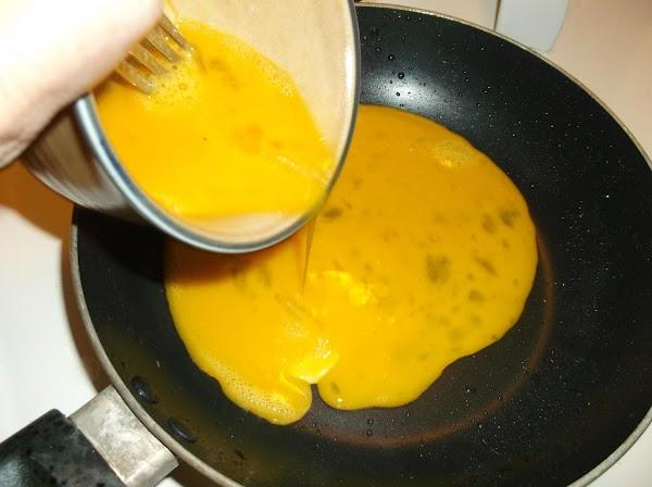 Place the skillet over medium heat; add beaten eggs.