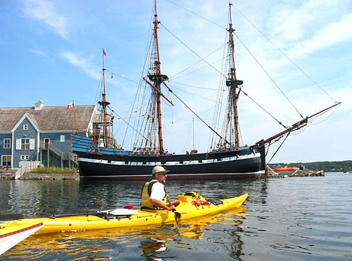 A kayaker heads out in front of the Hector, a replica that traces the region's Scottish heritage.