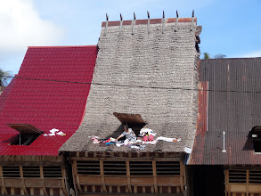 Photo: Each village home has a door in the roof to lay out the clothing on the roof to dry. This woman was collecting her dried laundry from the roof.