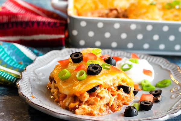 A Slice Of Creamy Cheesy Gooey Enchiladas On A Plate.