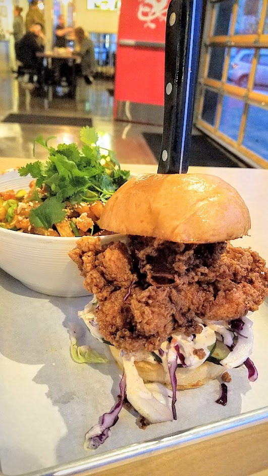 Basilisk Fried Chicken Sandwich with fried chicken thigh and house pickled cucumbers, shredded cabbage and special sauce that needs a knife stabbed through the middle to keep it together