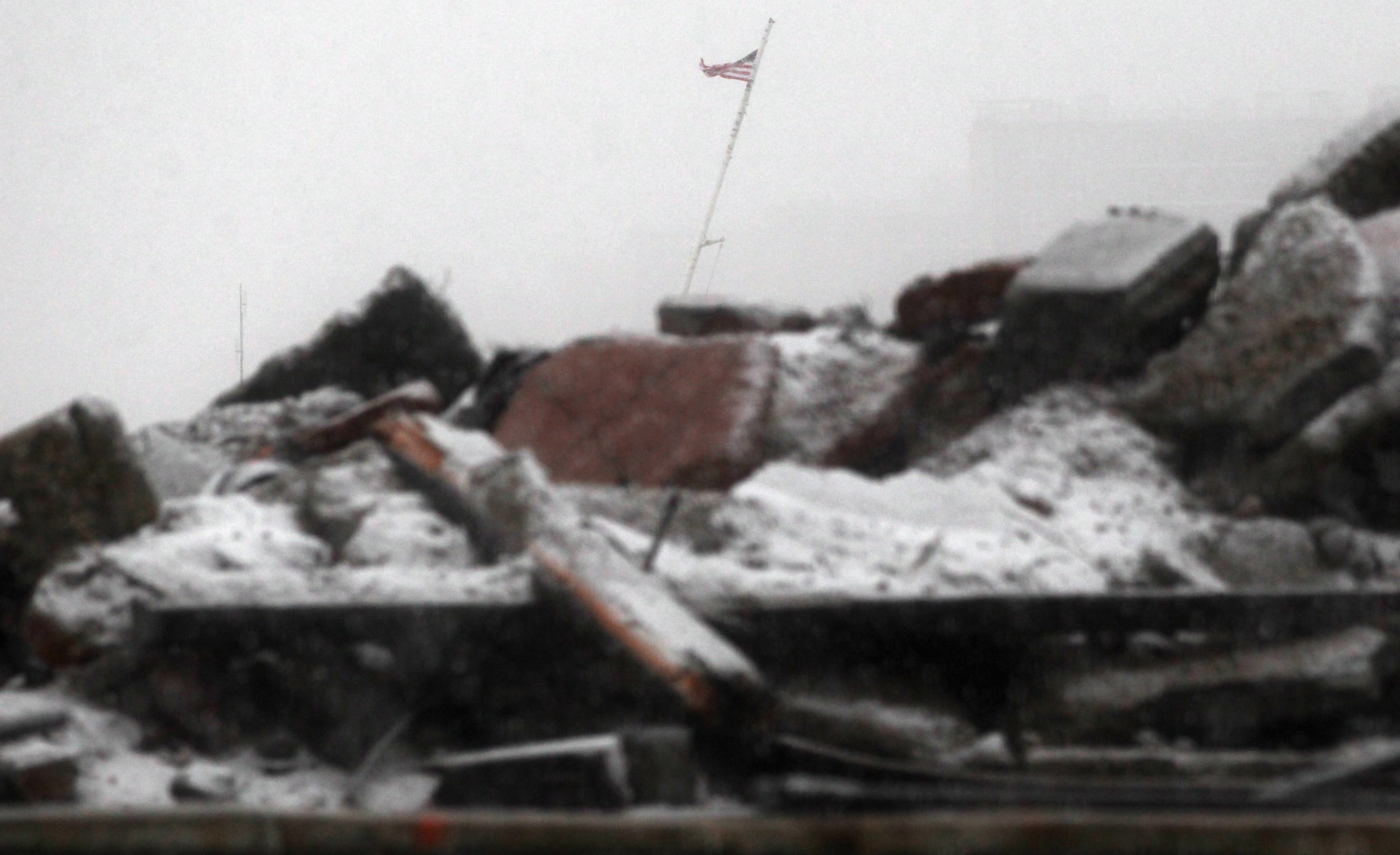 Photo: NEW YORK, NY - NOVEMBER 07:  Snow falls on debris with an American flag flying as a Nor'Easter arrives in the Rockaway neighborhood on November 7, 2012 in the Queens borough of New York City. The Rockaway Peninsula was especially hard hit by Superstorm Sandy and some are evacuating ahead of the coming storm.   (Photo by Mario Tama/Getty Images)