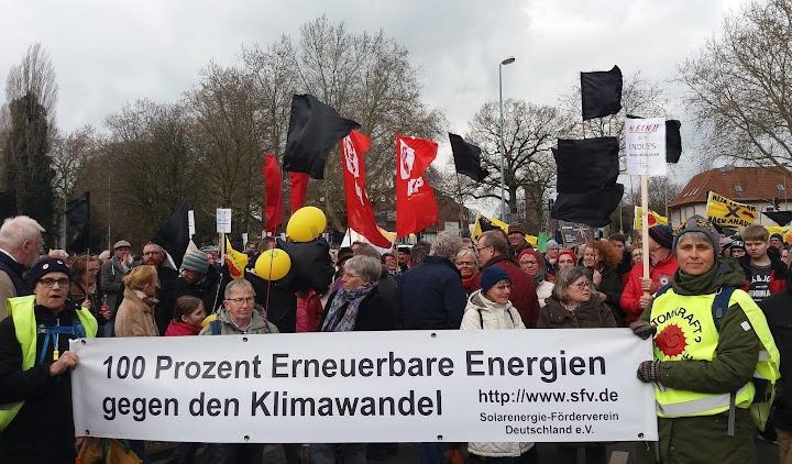 Demonstrant*innen mit Fahnen und Transparent: «100 Prozent Erneuerbare Energien gegen den Klimawandel!».