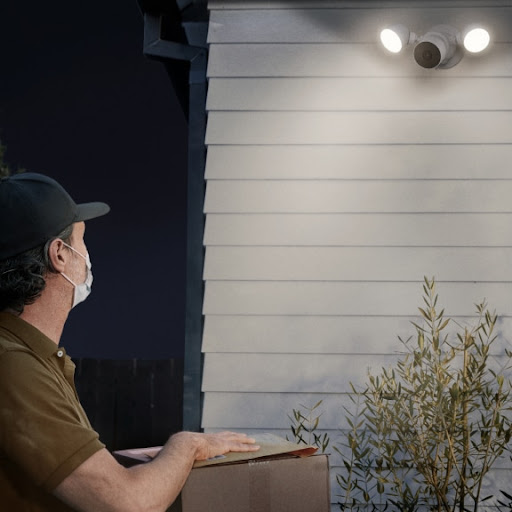 A delivery person approaches a house with a package.