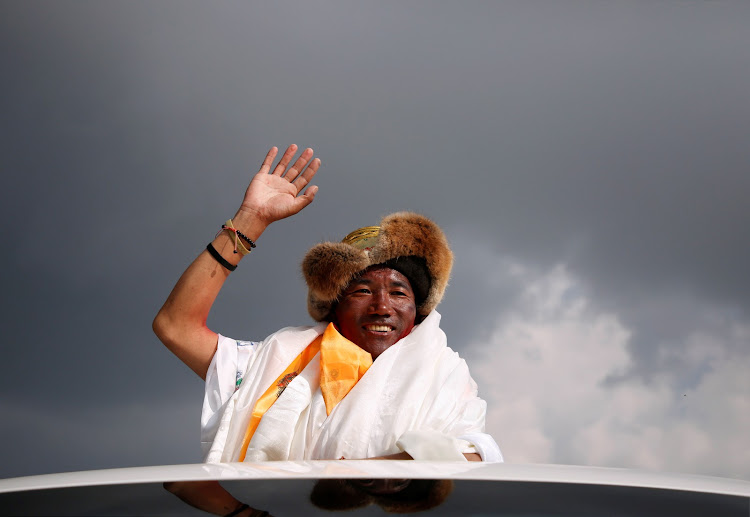 Kami Rita Sherpa, 48, a Nepali sherpa, waves after returning from climbing Mount Everest for a 22nd time, a new record for the most summits of the world's highest mountain.