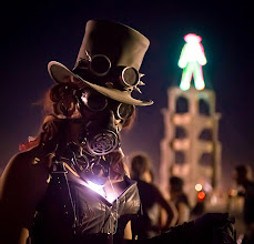 Photo: Steampunk at Burning Man   Everyone at Burning Man is in costume all the time. That's about 50,000 people at a week-long costume party that becomes pretty intense. On the night of the actual burn of the tower (which you can see in the background), there was a little gathering of steampunk players toward the inner ring. One of the girls saw me taking photos, and came over to compare goggles for a bit. I grabbed this one of her just before it was time to return to her party.  from Trey Ratcliff at http://www.StuckInCustoms.com