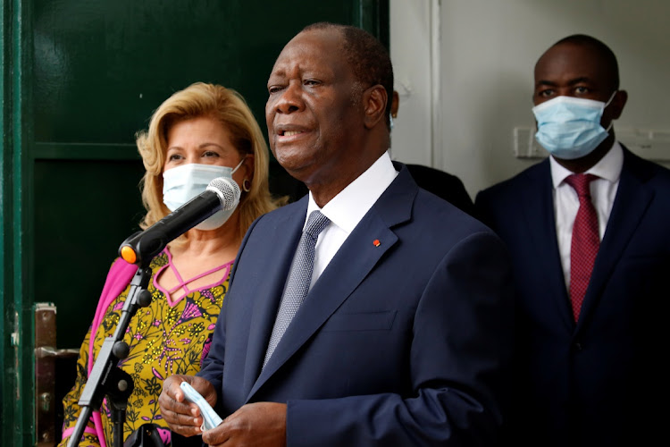Ivory Coast President Alassane Ouattara speaks next to his wife Dominique after casting their votes at a polling station during the presidential election in Abidjan, Ivory Coast October 31, 2020.
