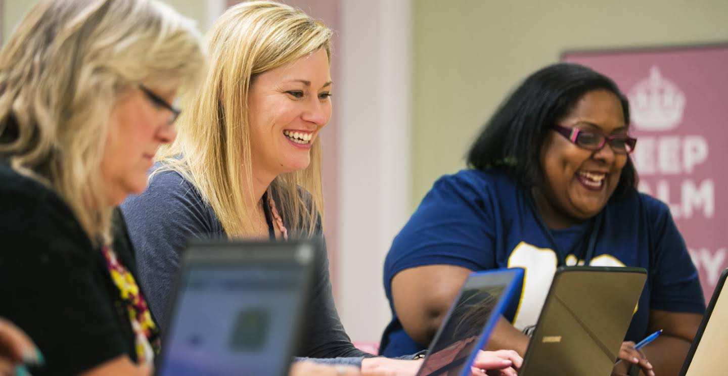 Three female educators smiling in front of their laptops.